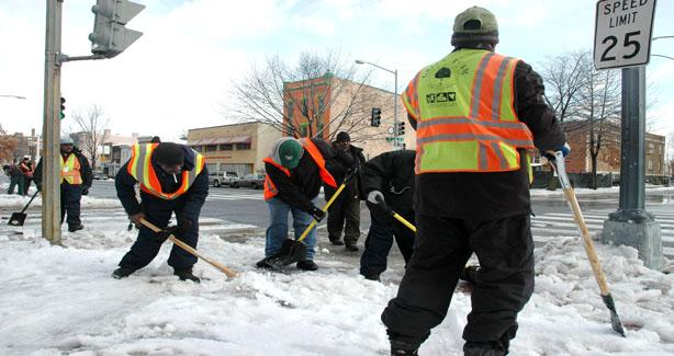 Group of workers shoveling snow