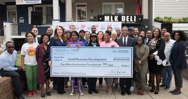 DSLBD and business owners holding large check