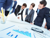 Group of people in business attire standing over a table with charts