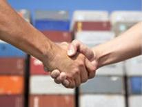 Two arms reaching in a handshake with shipping containers in the background and out of focus