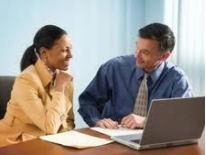 Smiling man and woman in a meeting room sitting in front of a computer with documents