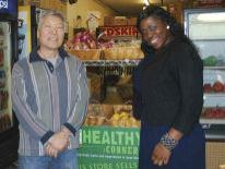 Smiling man and woman in a food market standing in front of a food stand with a green sign with the word Healthy Corner on it